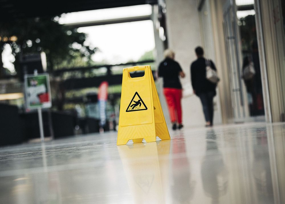 A wet floor sign is seen in the foreground while people walk in front of an office building in the background.