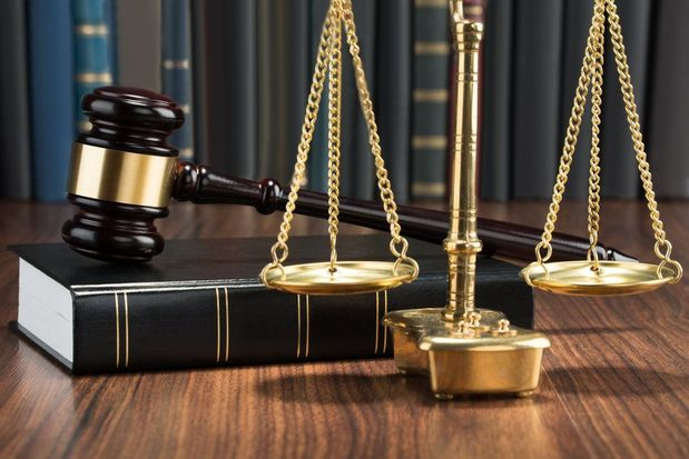 Justice scale, gavel, and law book resting on a table.