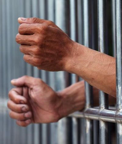 A person's hands sticking out of a jail cell
