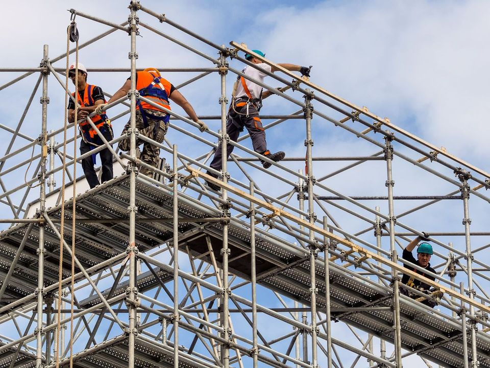 Construction workers in scaffolding