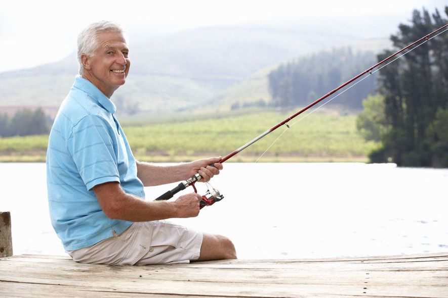 An elderly man sitting on a dock, fishing.