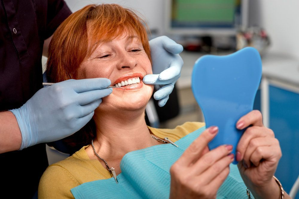 A female patient looking at her new smile in the mirror after full mouth reconstruction.