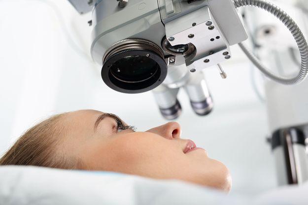 Female refractive surgery patient lying under machine