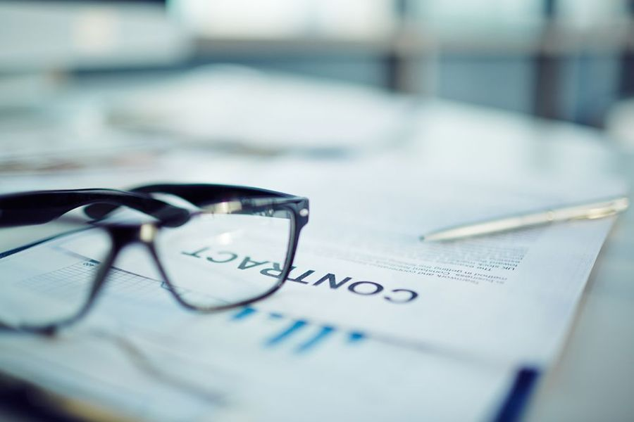 A contract on a table with eyeglasses in the foreground
