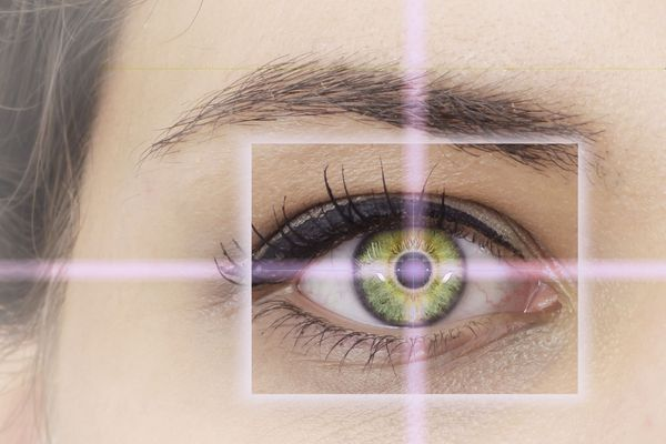 A close up image of a green eye in the crosshairs of a laser