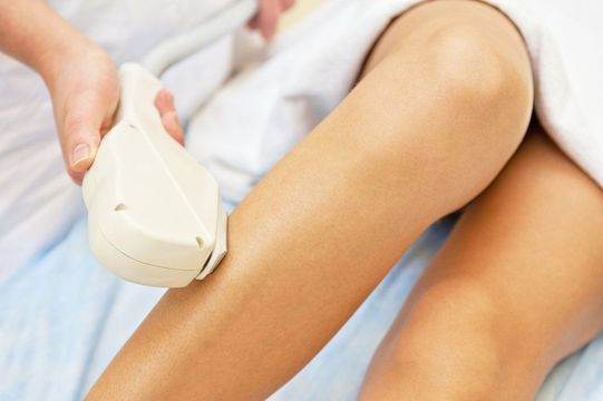 A woman undergoing laser hair removal on her leg