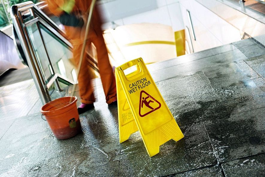 Man washing floor next to caution sign