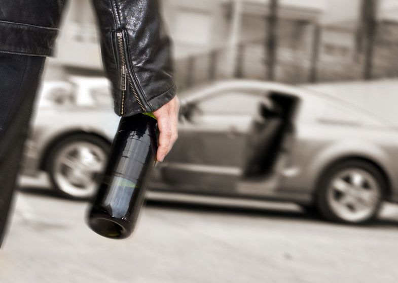 Man in leather coat walking towards car with wine bottle in his hand