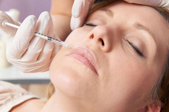 Woman lying down with eyes closed receiving an injection in her face
