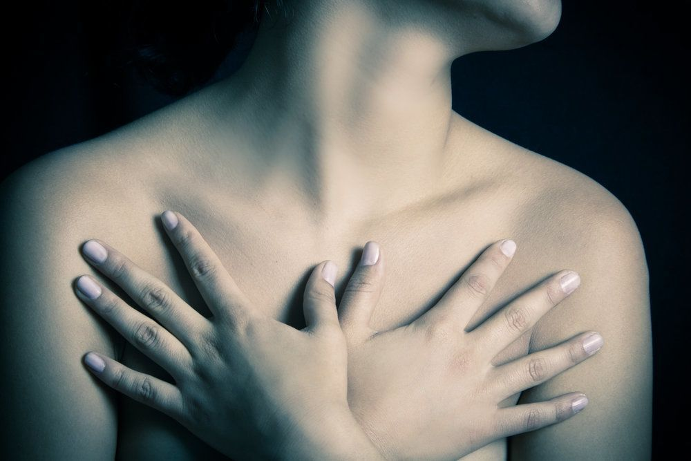 A picture of a woman from the neck down with her hands over her breasts