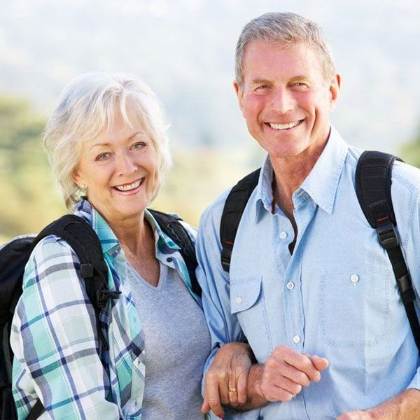An older couple locks arms and smiles at the camera.