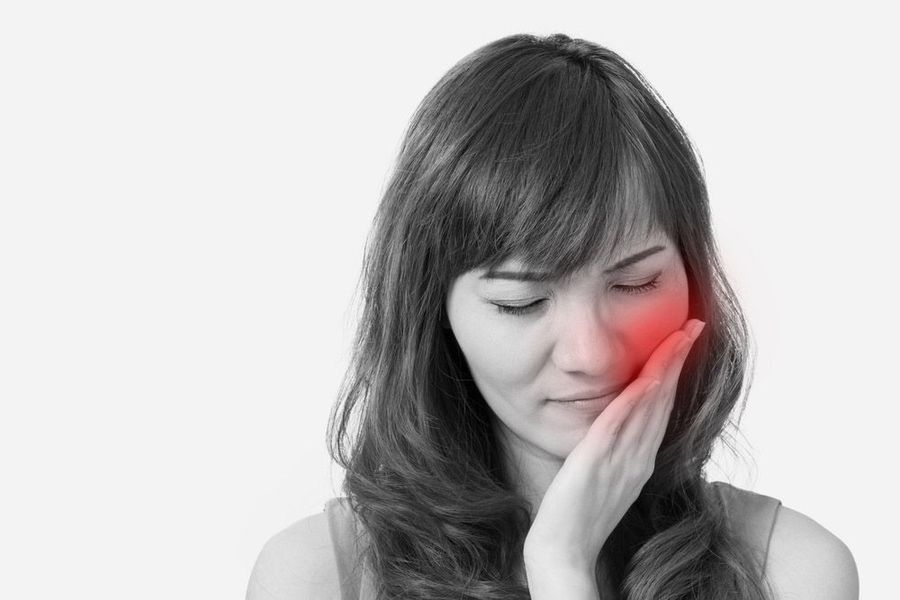 Woman holding jaw marked in red to indicate pain