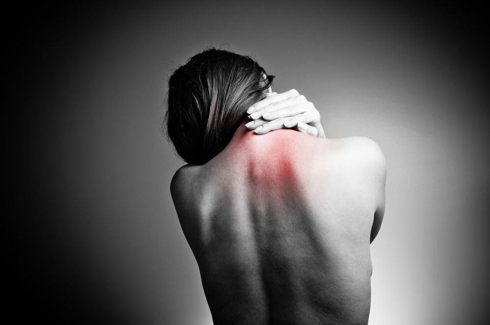 Photo of woman holding neck in pain