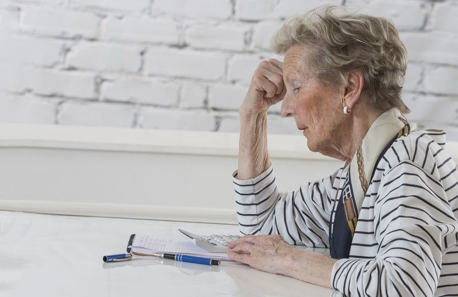 An older woman sitting at a table alone
