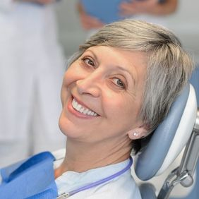 A grey-haired woman sitting in the dentist's chair