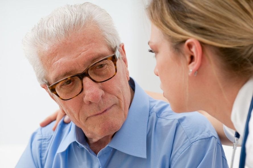 An elderly man speaks closely with his doctor.