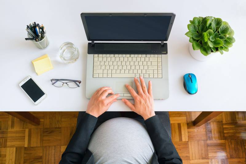 Bird's eye view of pregnant woman at computer