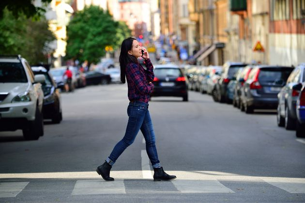 Pedestrian talking on the phone while she crosses the street