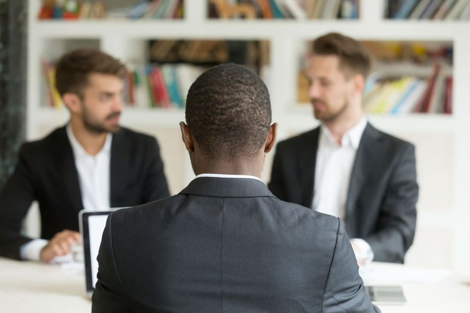 A black man sits at a desk in front of two white men who are in deep discussion.