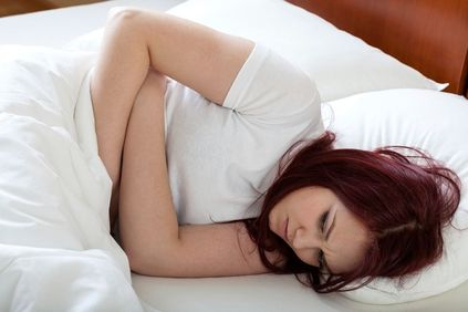 Red-headed woman lying on side in bed and holding stomach in pain