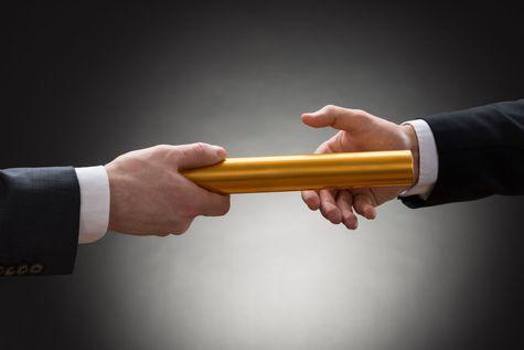 Businessmen passing golden baton