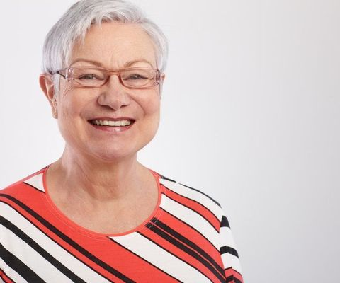 A smiling grey-haired woman in glasses