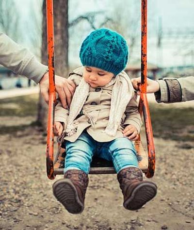 Child on swing set between two parents