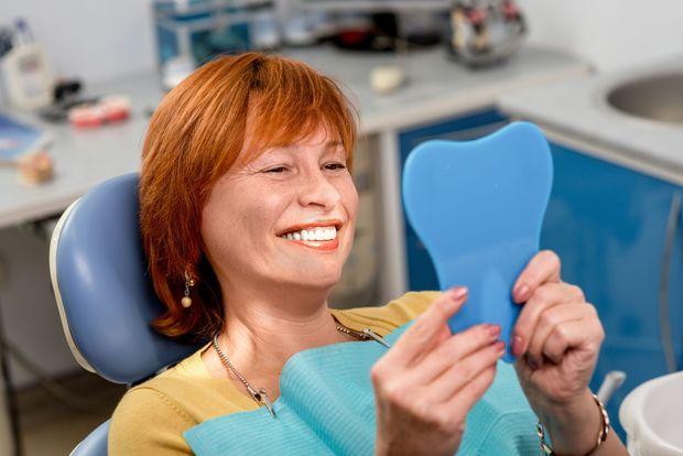 Smiling woman looking at teeth in dental mirror
