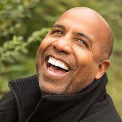 Laughing man wearing black zippered turtleneck sweater